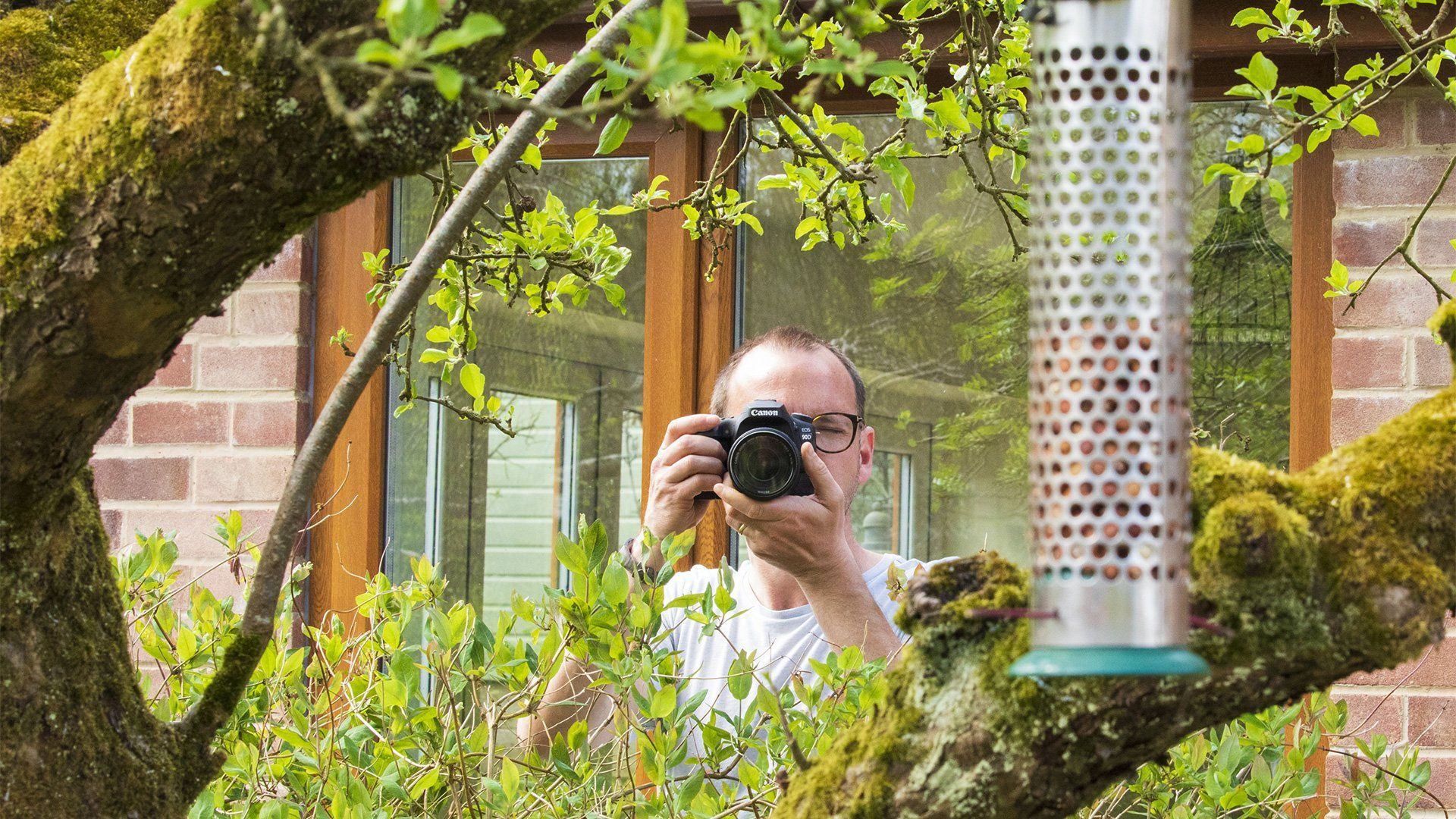 James Paterson photographing a bird feeder in his garden.